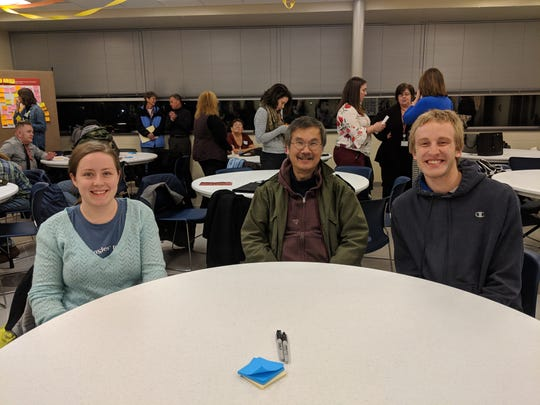 From left, East Price Hill residents Lydia Faber and Dan Wong, and Ben Klayer from West Price Hill. Price Hill residents pick a seat minutes before the meeting begins.