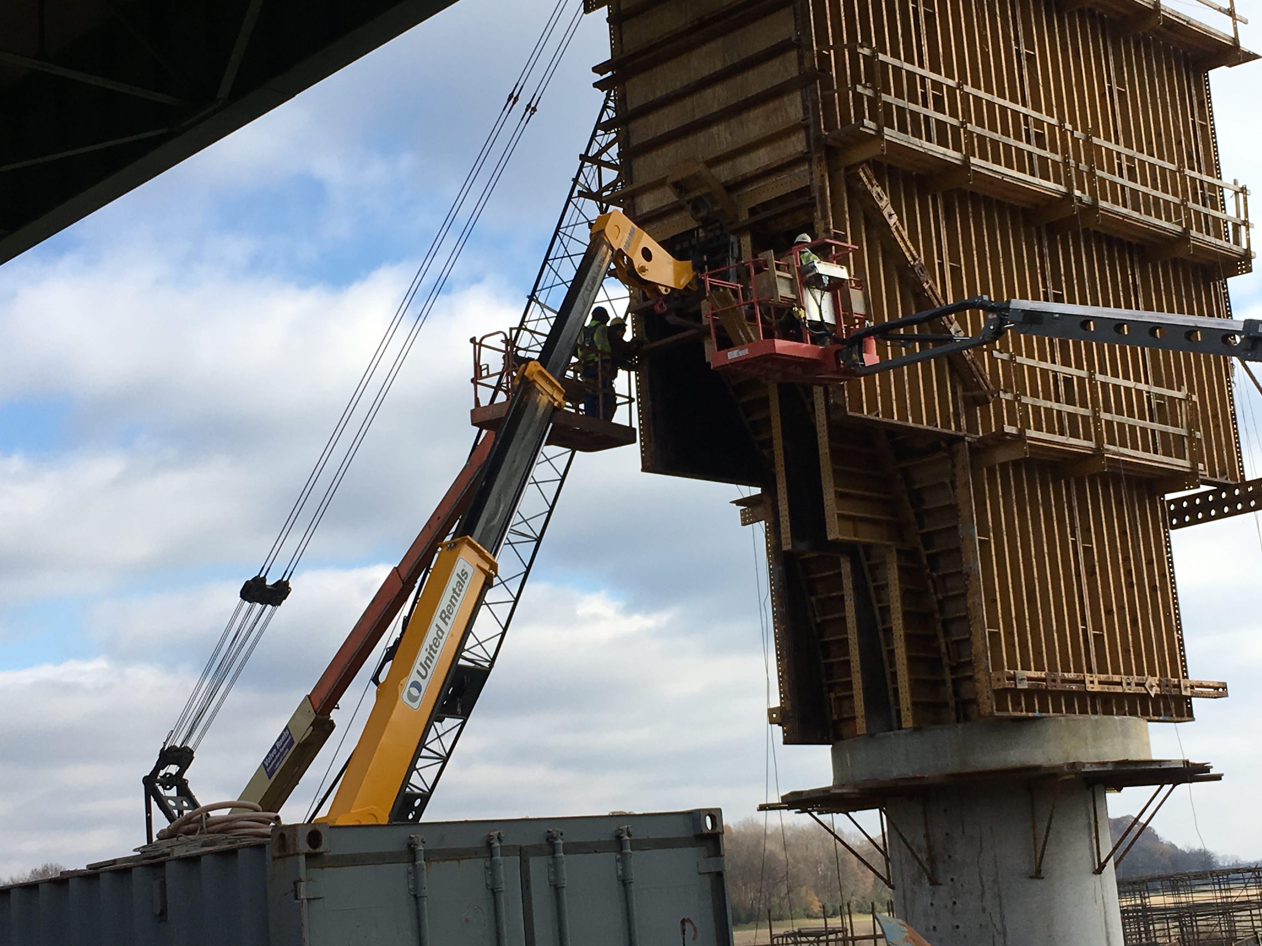 Workers detach a concrete form around a bridge support pier.