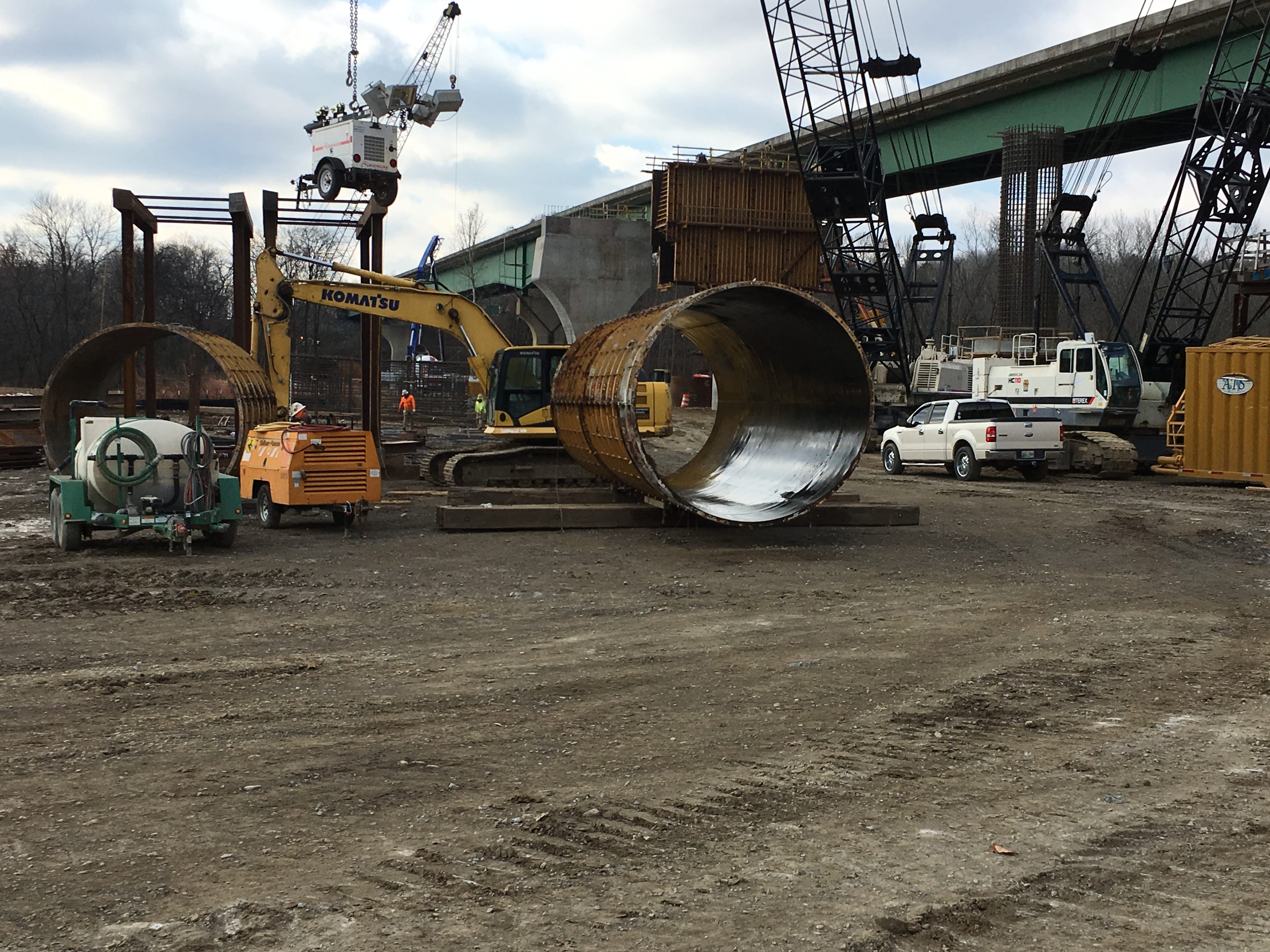 Large, round metal concrete forms await placement to construct support piers.