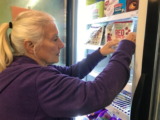 Tree of Life Market employee Jill Torrence stocks organic berries in the frozen food section of the Clarksville store. It will be closing permanently Dec. 22.