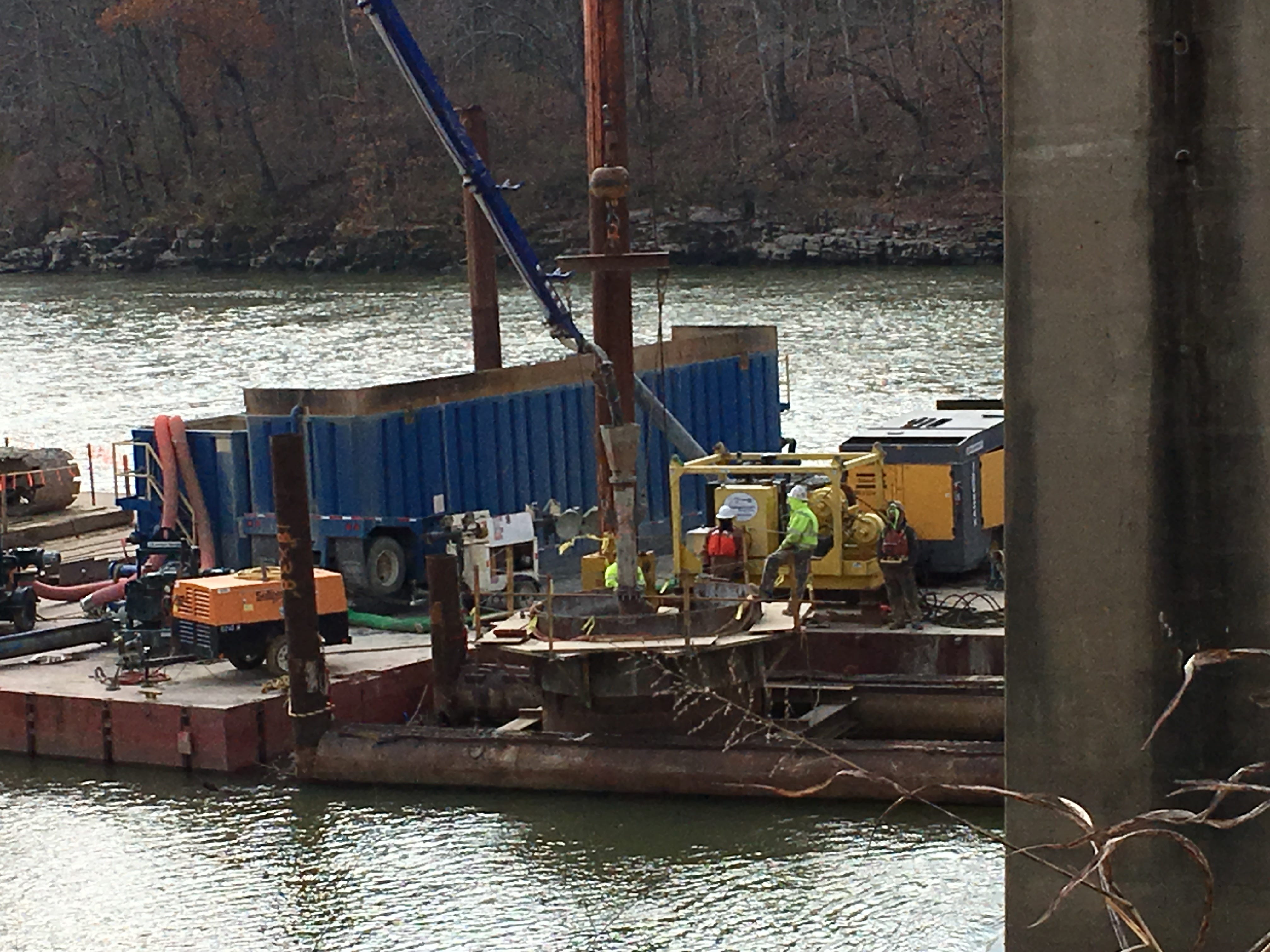 Workers monitor concrete being pumped into a shaft that will support a bridge pier in the Cumberland River.
