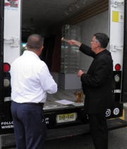 Bishop James F. Checchio, leader of the Diocese of Metuchen, blesses a truck owned by Mark Maher at the St. John Neumann Pastoral Center in Piscataway Oct 4, the feast of St. Francis of Assisi. Maher, who opened Trinity Church Goods 13 years ago in Raritan Borough has morphed it into CatholicGear.com – an online store with a mobile retail truck that will travel around the diocese.