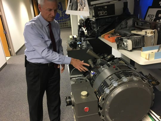 Dave Busiek, retiring news director at KCCI-TV, demonstrates an old film editor like the ones used at the beginning of his career in 1979. Busiek retires at the end of the year after nearly 40 years at the CBS affiliate.