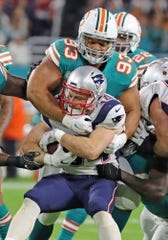 Miami Dolphins' Ndamukong Suh tackles New England Patriots' Rex Bulkhead in the first quarter at Hard Rock Stadium, Dec. 11, 2017 in Miami Gardens, Fla.