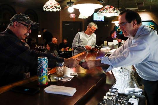 Miller's bartender Jeff Robinson gives change back to customer Bill Baker at the restaurant in Dearborn, Tuesday, Nov. 27, 2018.