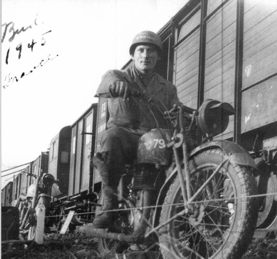 While in the  army, Bill Brown rides a motorcycle in France, checking on supplies next to a train in 1945 during WWII.