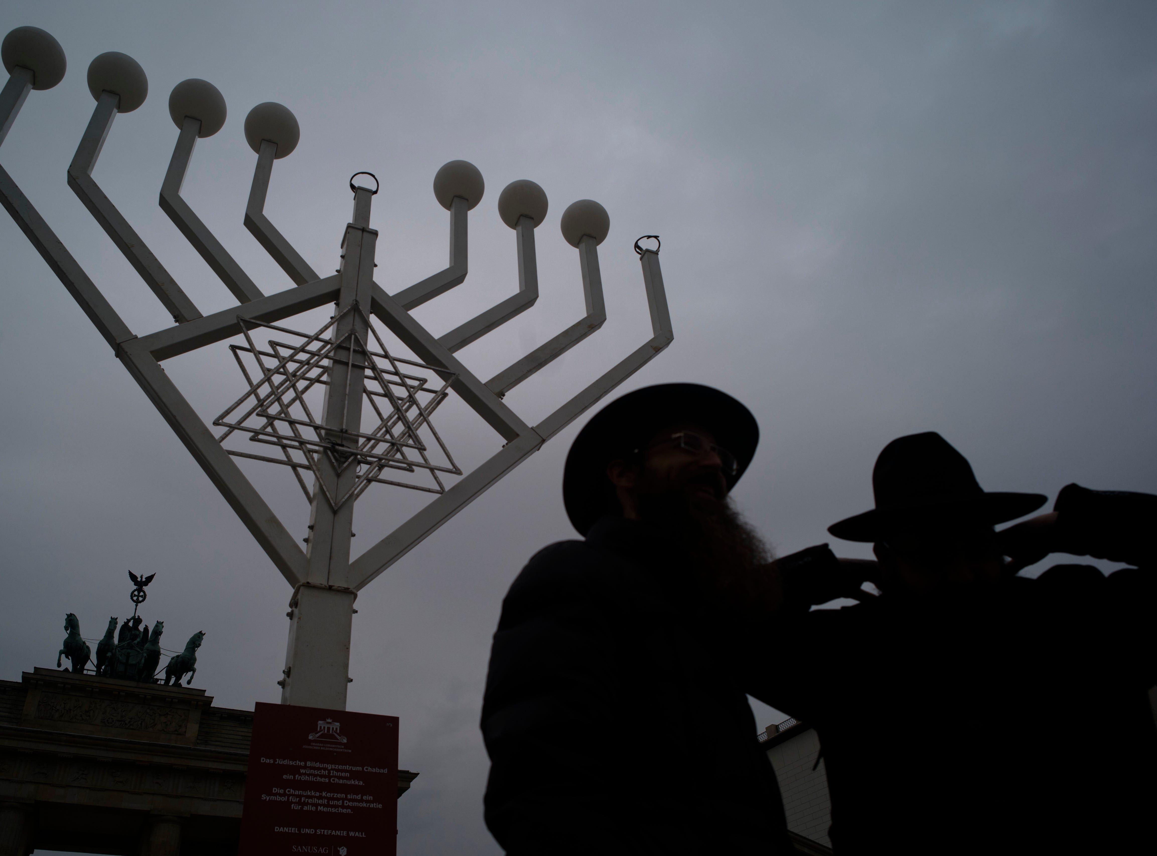 Rabbi Yehuda Teichtal, right, and Rabbi Segal Shmoel, left, inspect a giant Hanukkah Menorah, set up by the Jewish Chabad Educational Center ahead of the Jewish Hanukkah holiday, at the Pariser Platz in Berlin, Germany, Friday, Nov. 30, 2018.