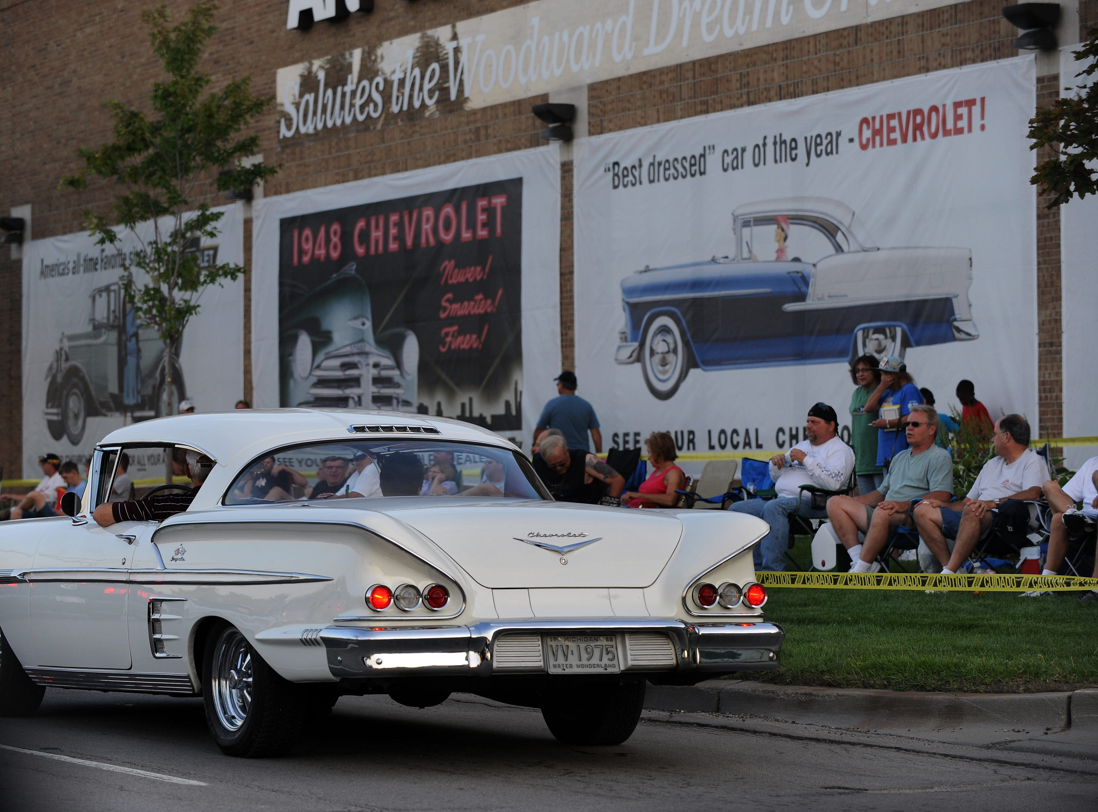A white Chevy Impala motors past vintage Chevy ads decorating the side of the Art Van Furniture on Woodward in Royal Oak, Aug. 19, 2011.