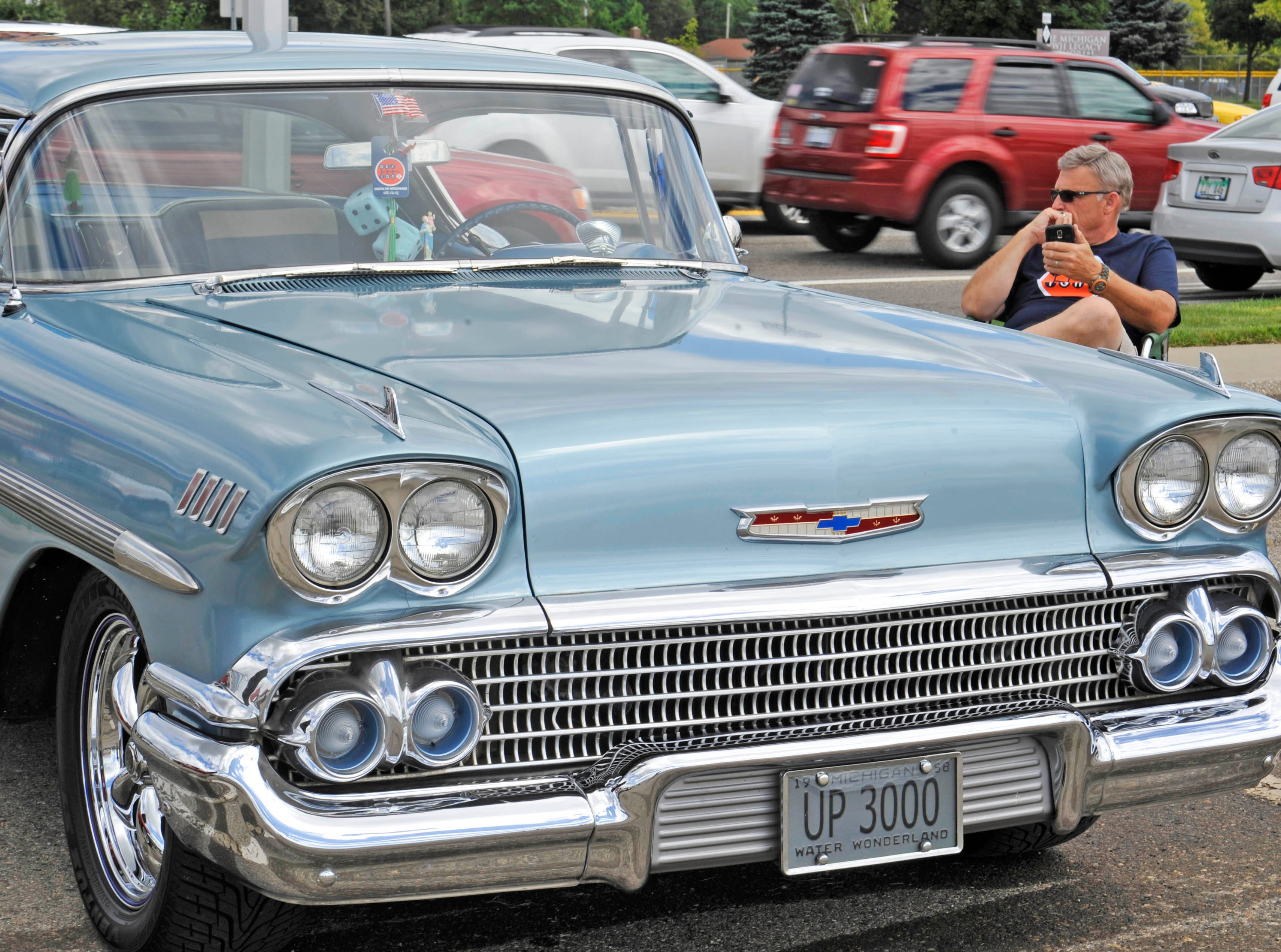 Al Bitell of Livonia sits with his 1958 Chevrolet Impala during a design show as part of the Woodward Dream Cruise at 13 Mile and Woodward in Royal Oak, Aug. 12, 2015.