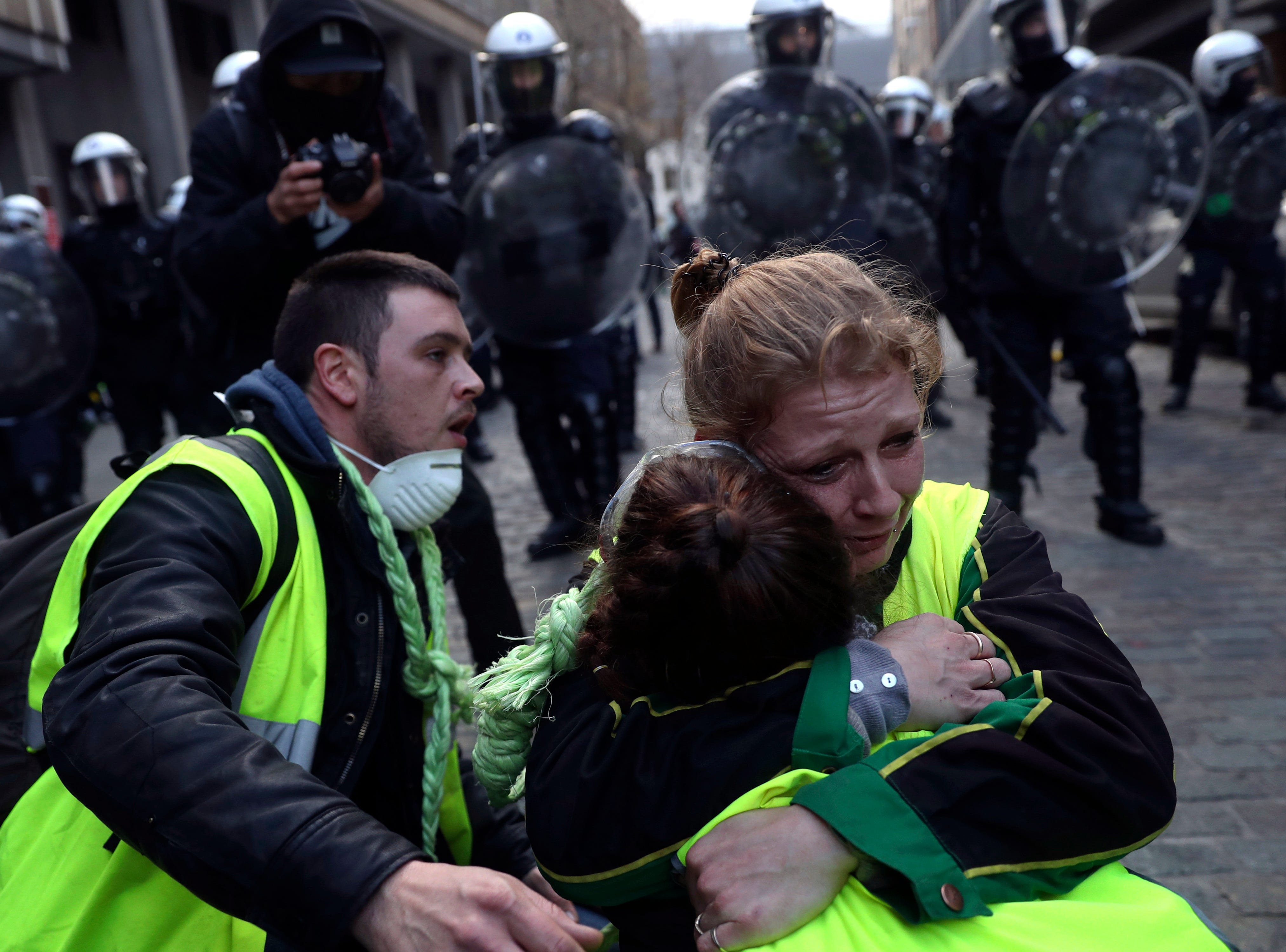 Protestors hug each other in front of a line of anti riot policemen during a protest of the yellow jackets in Brussels, Friday, Nov. 30, 2018. The demonstrators are protesting against rising fuel prices.
