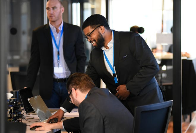 Following a ribbon-cutting ceremony for the new Accenture Detroit office, Accenture employee Carlos Shows, standing in the foreground, prepares to give a demonstration to visitors.