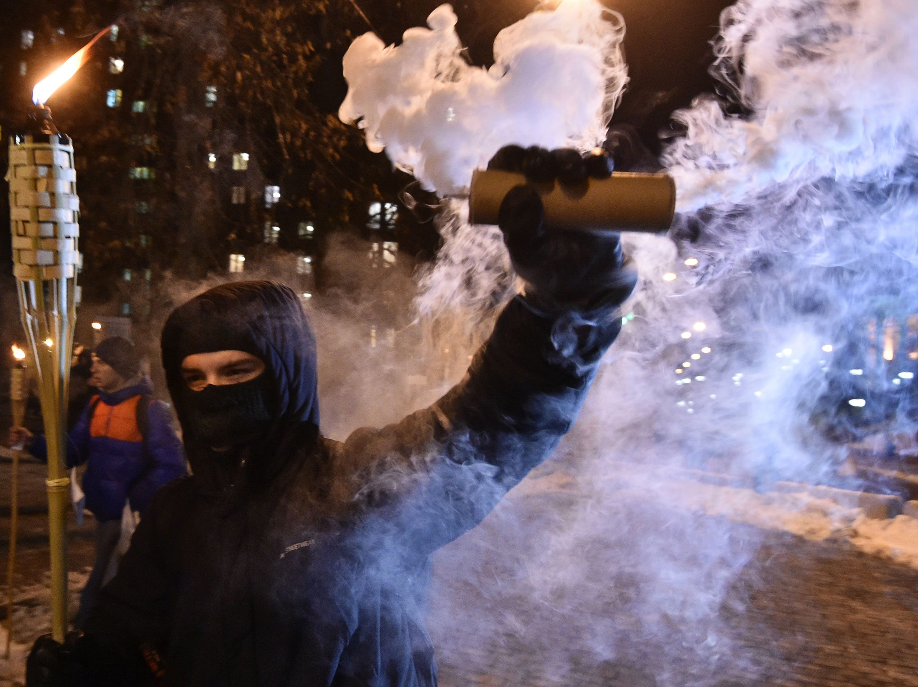 A protester holds a torch and a smoke flare during a march in the Ukrainian capital Kiev on November 29, 2018, to ask for justice for protesters killed on Kiev's Maidan square in 2014 during the 'Maidan' revolution, which ousted a pro-Moscow government but sparked war in the east of the country and led to Russia annexing Crimea.
