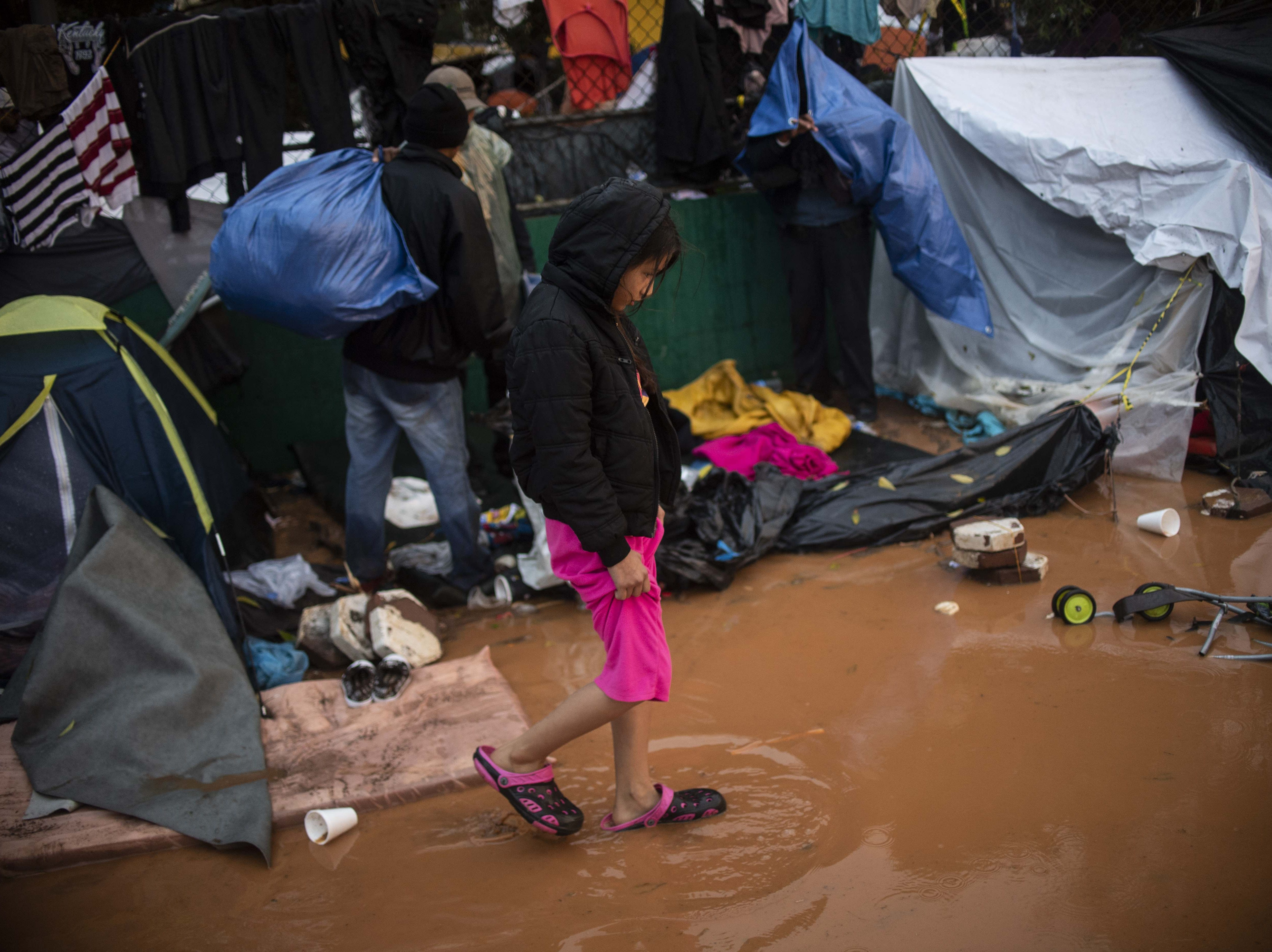 A girl who trekked for over a month across Central America and Mexico within a caravan of Central American migrants, mostly Hondurans, in the hopes of reaching the United States, walks in the water at the temporary shelter in Tijuana, Baja California State, Mexico, near the border with the US, after heavy rain on November 29, 2018. - Members of the Central American migrant caravan are starting to lose hope, and in some cases are turning back after more than a month's trek. Their surprise bid to rush the border en masse on Sunday ended as abruptly as it began, when US Border Patrol agents fired tear gas and rubber bullets to force them back.