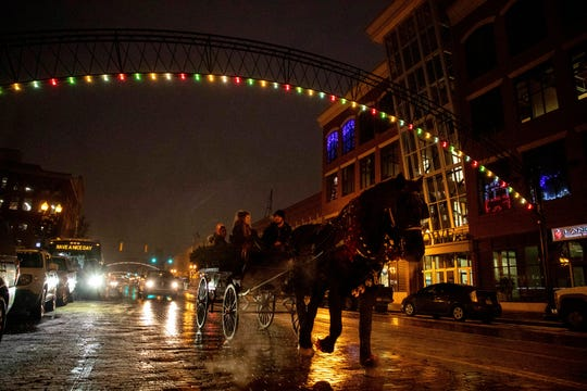 A carriage makes its way down Saginaw Street during the Christmas tree lighting celebration on Thursday, Nov. 29, 2018, in downtown Flint, Mich.