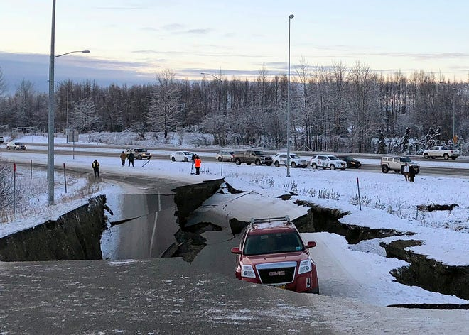 A car is trapped on a collapsed section of the offramp of Minnesota Drive in Anchorage, Friday, Nov. 30, 2018.