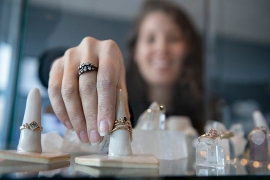 Elaine Jaeger, owner of Elaine B. Jewelry, in Ferndale, adjusts jewelry in a display case in her store.
