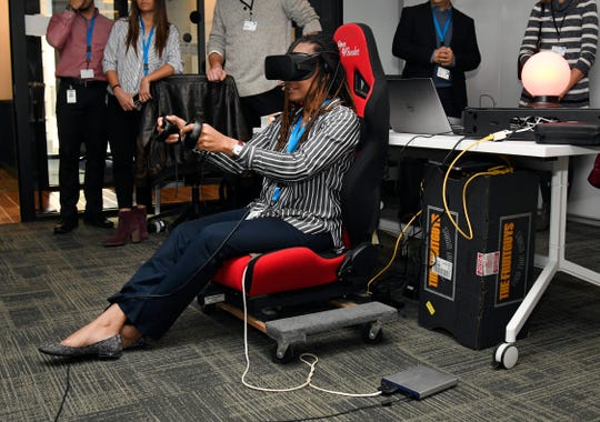 Following a ribbon cutting ceremony for the new Accenture Detroit office, Accenture employee Michallene Thacker-Mann sits in a motion sensing chair and tries on a virtual reality device that makes her think she is in the driver's seat of an automobile.  Photo taken on Friday, Nov. 30, 2018.