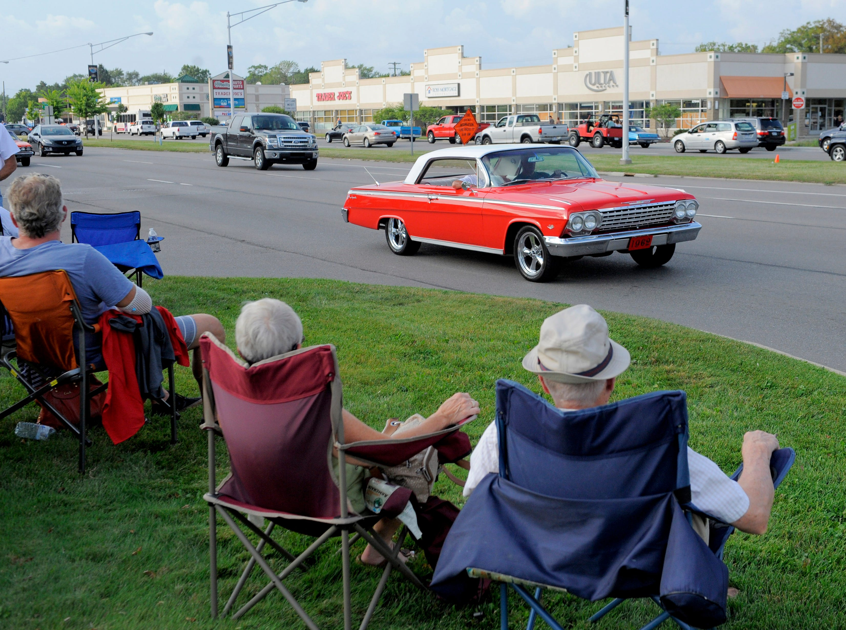 A 1962 Chevrolet Impala passes by several spectators, Friday Aug. 14, 2015, on Woodward near 11 Mile in Royal Oak.