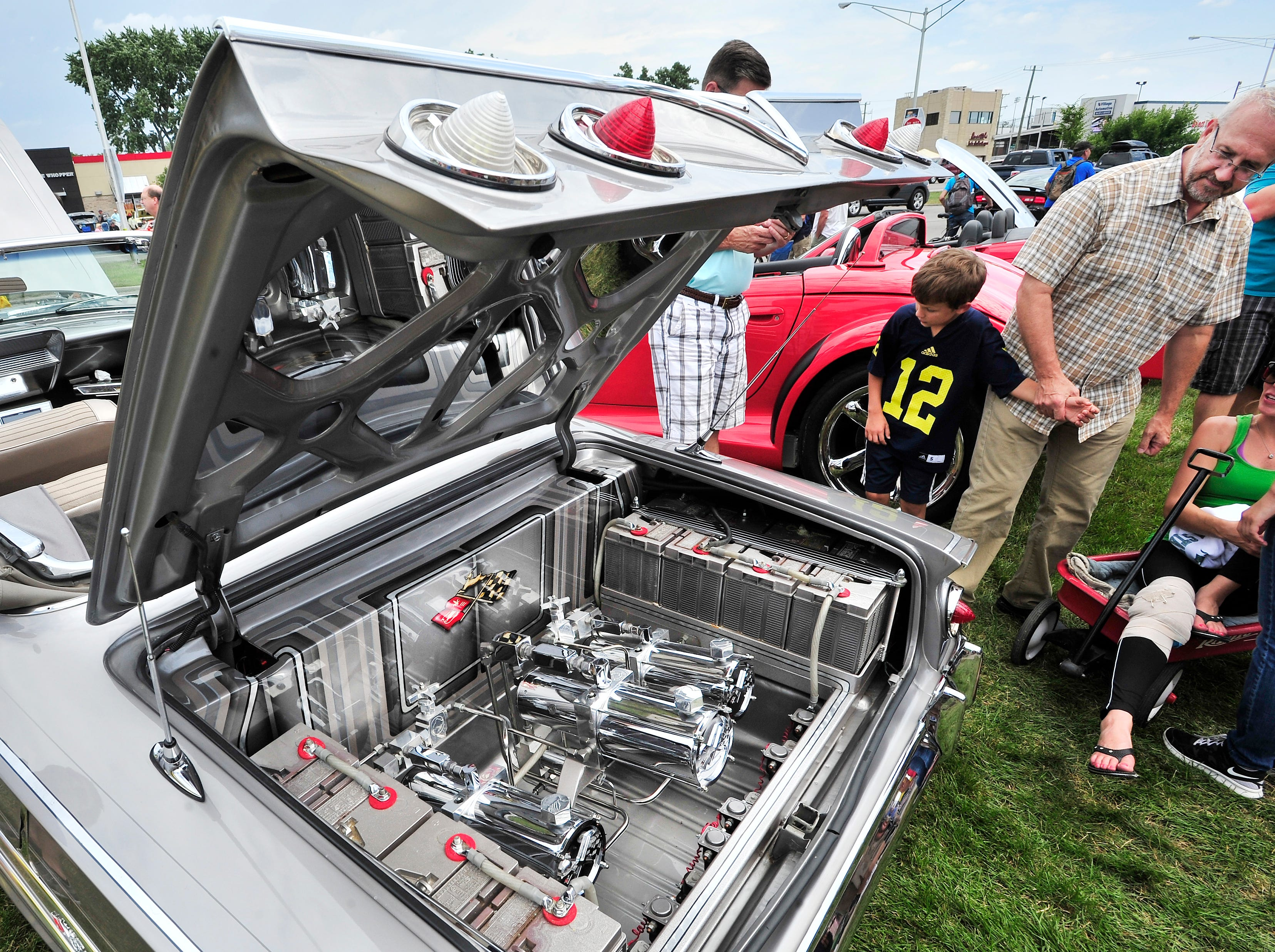 "An open trunk of an Impala with batteries and hydraulics draws stares. ""A '61 amazing Impala"" says Daniel Zaid as he looks over the spotless, chromed-out engine during the Woodward Dream Cruise in Royal Oak, Aug. 16, 2014."