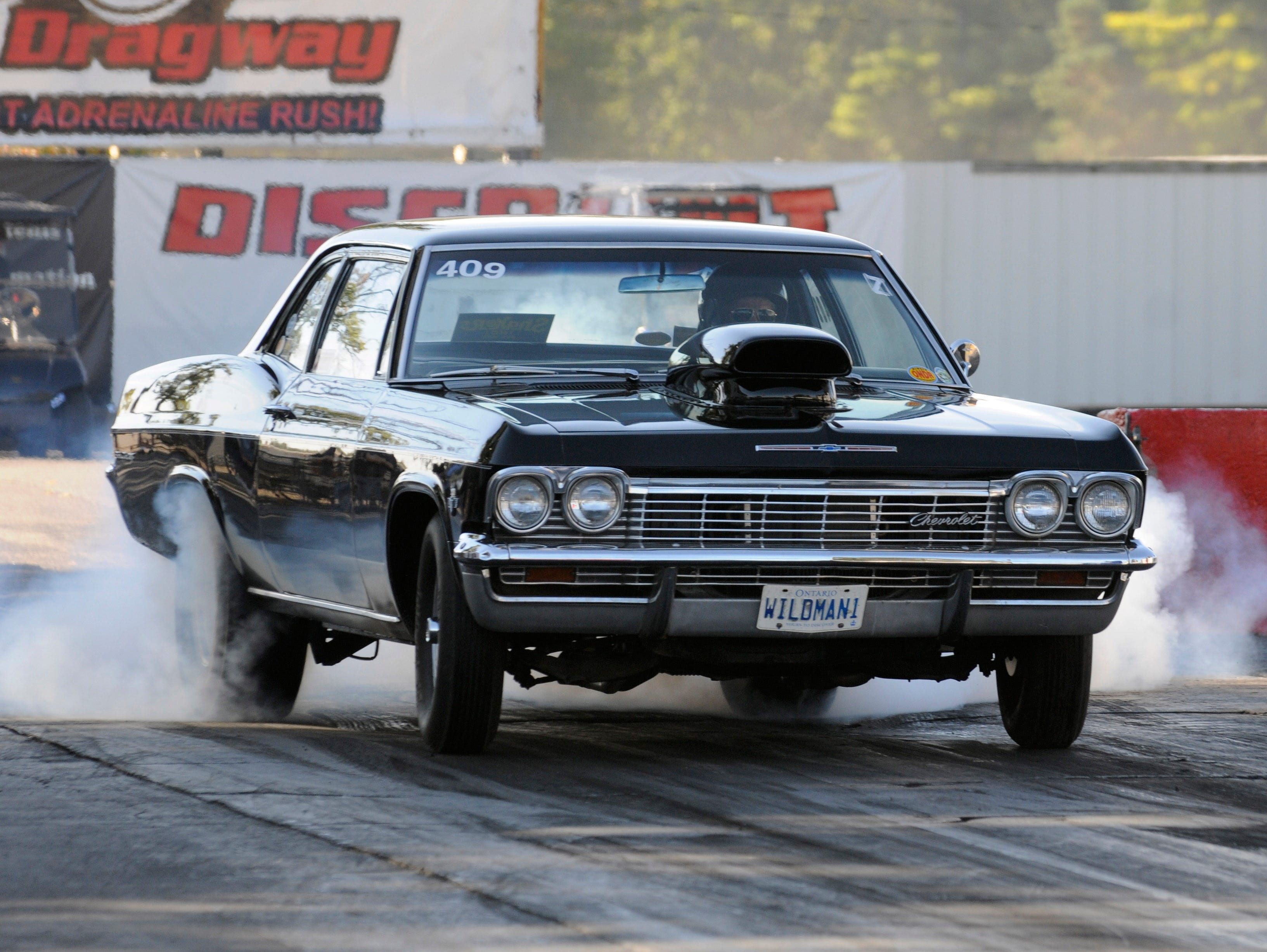 Bob Walker of Windsor performs a burnout in his 1965 Chevrolet Impala with a 409 cubic inch engine, Saturday Sept. 27, 2014, during nostalgia drag racing at Milan Dragway in Milan.
