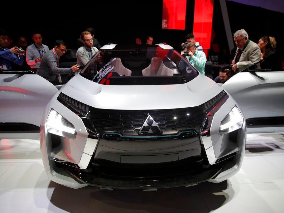 Attendees look at the Mitsubishi e-Evolution concept at the Los Angeles Auto Show Wednesday, Nov. 28, 2018, in Los Angeles.
