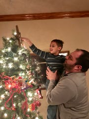Michael helps Miles place the star on the top of their Christmas tree.