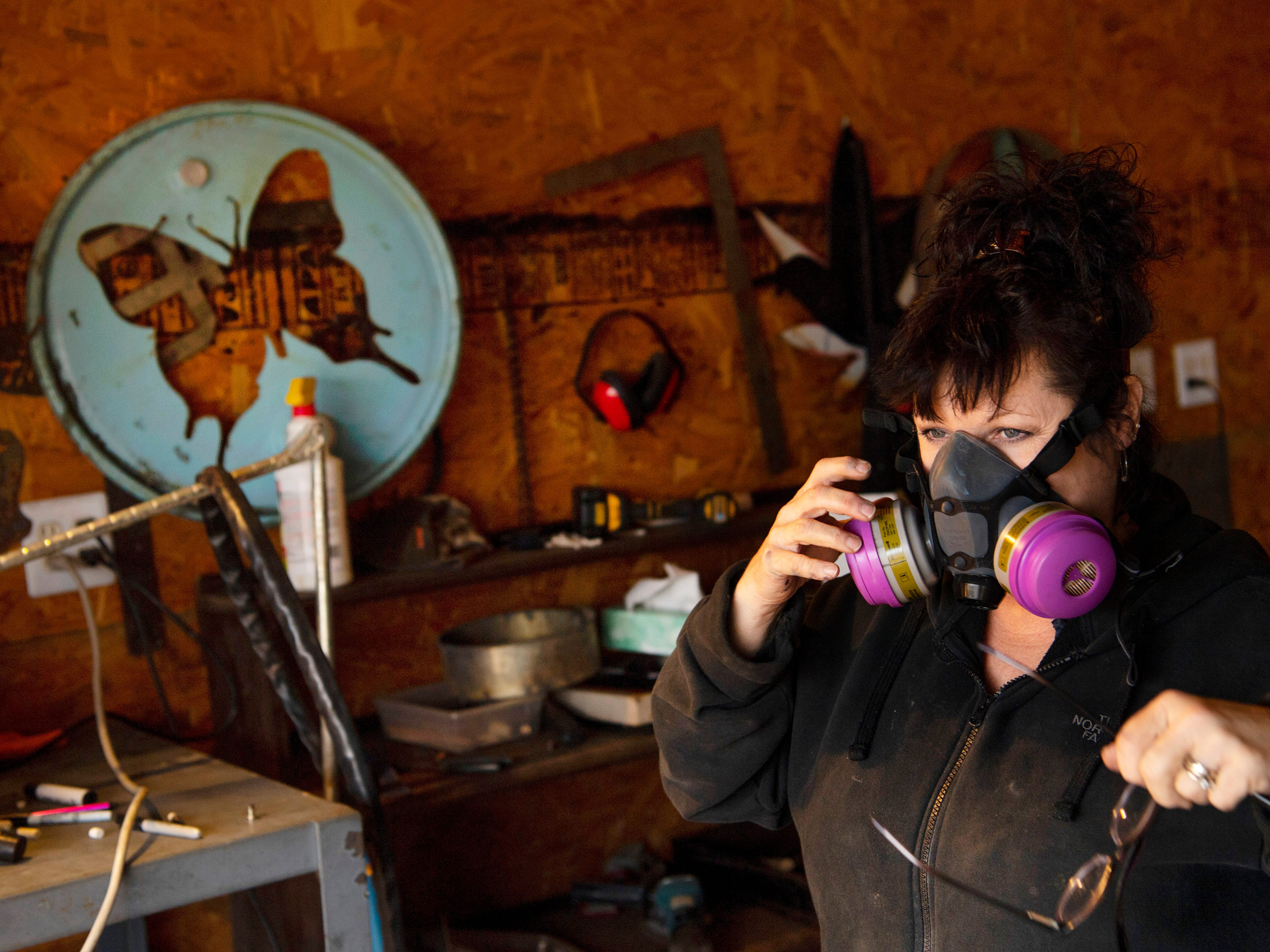 Tammy Trem removes her breathing apparatus after creating hand saw wall art with her plasma torch at Salvage Candy in Evansville Friday afternoon. Trem makes custom metal artwork for clients which can include Christmas trees, pets, butterflies and even the hostess station at Comfort by the Cross-Eyed Cricket downtown.