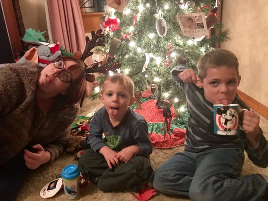 Abbey, Owen and Miles take a silly break while decorating the Christmas tree.
