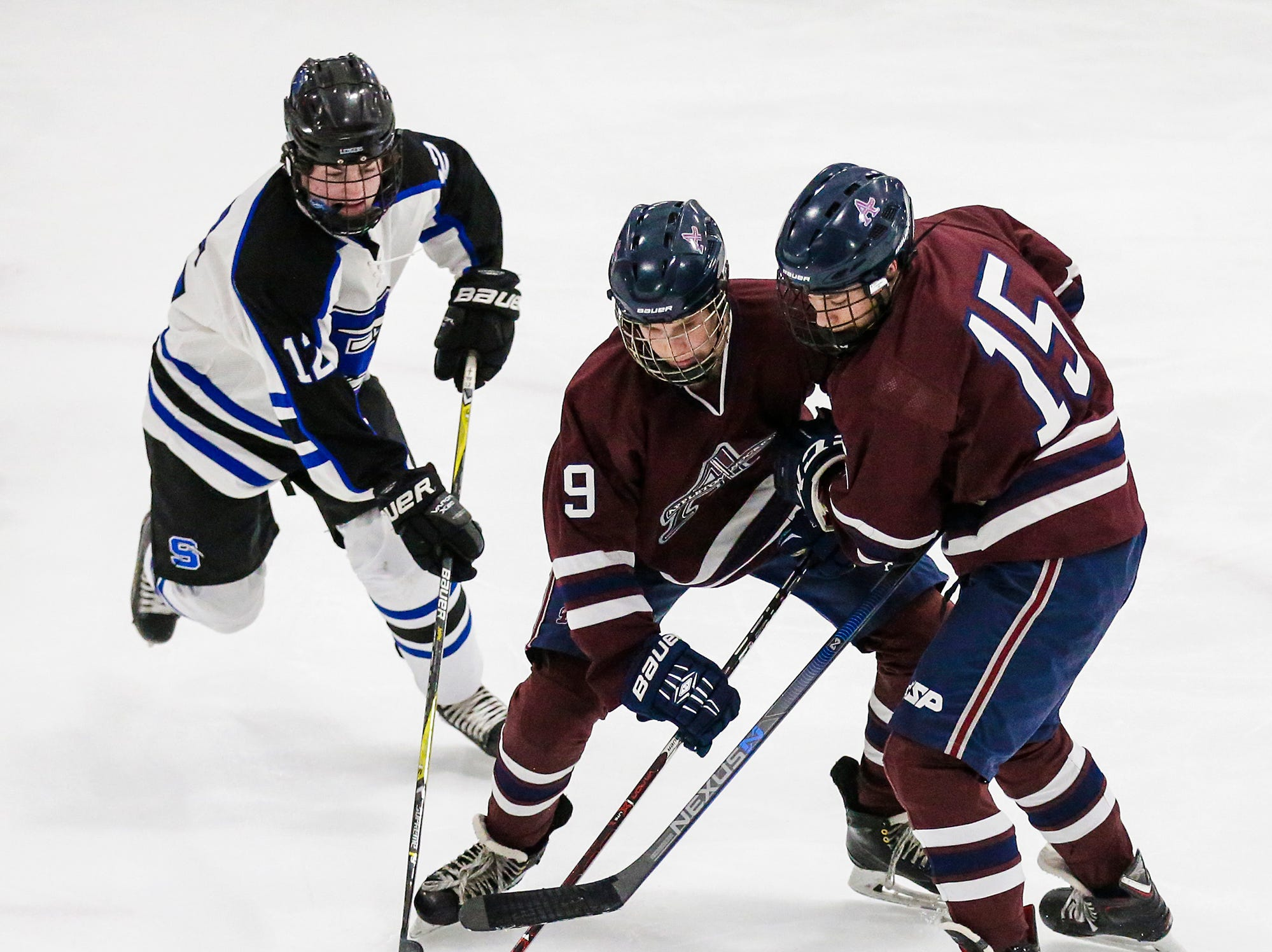 St. Mary's Springs Academy co-op hockey's Mitchell Huettl tries to get the puck from Appleton United's Jack Moeller (9) and Brenden Ryan (15) during their game Thursday, November 29, 2018 played in Fond du Lac. Springs won the game 8-1. Doug Raflik/USA TODAY NETWORK-Wisconsin