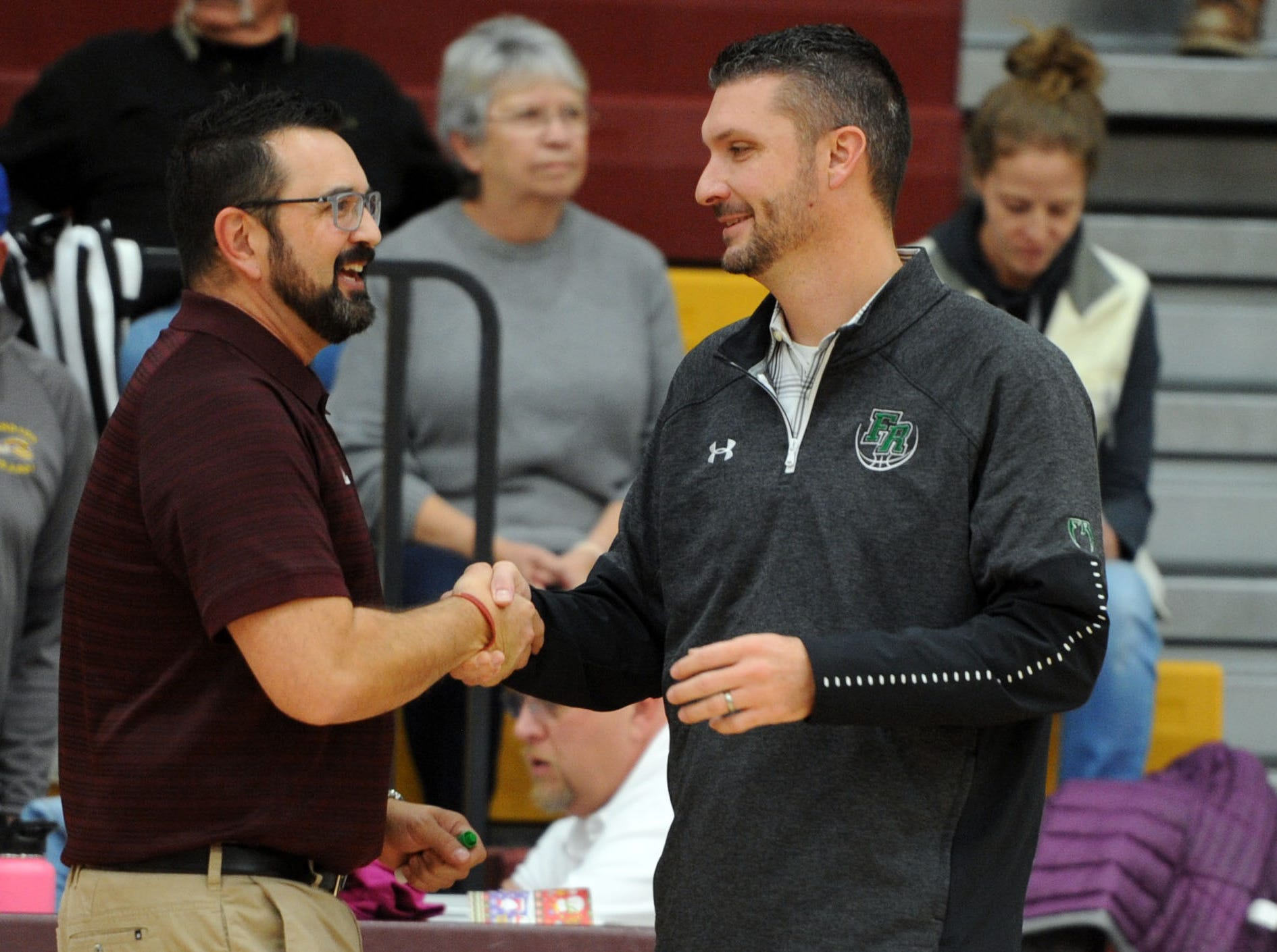 Windsor head coach Jim Porth, right, greets Fossil Ridge head coach, Chad Salz, before the game Thursday at Windsor High School.