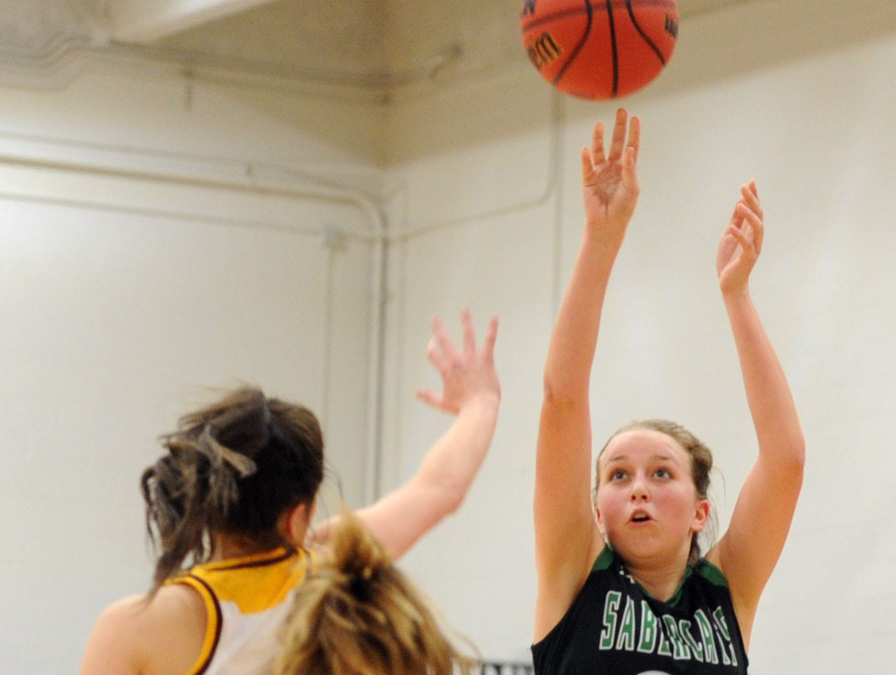 Fossil Ridge's Allison Osthoff makes a shot over Windsor's Valerie Apodaca and Ally Kennis during the game Thursday at Windsor High School.