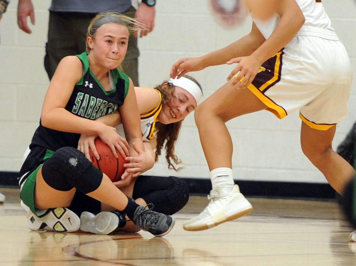 Fossil Ridge's Davin Tonn tries to wrestle the ball away from Windsor's Kylie Sanger during the game Thursday at Windsor High School.