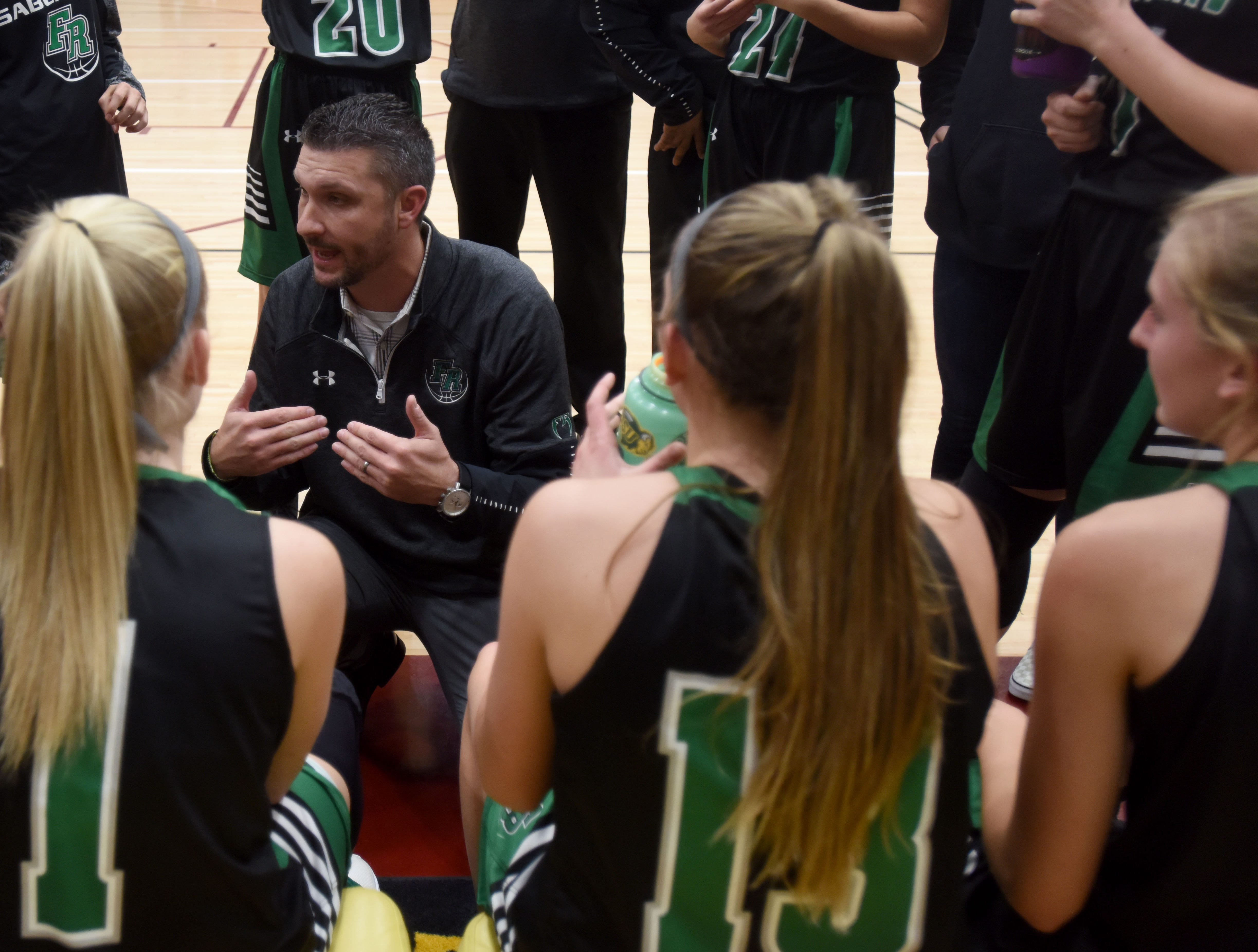 Fossil Ridge head coach, Chad Salz, talks to his players during the half.