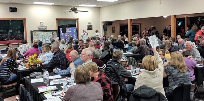 Auctioneer Joe Lafortune signals recognition of a bid by a woman at Holy Trinity Parish's annual auction on Nov. 10 in Oconto. Assisting LaFortune were Connor Huggett and Joe's wife Janelle.