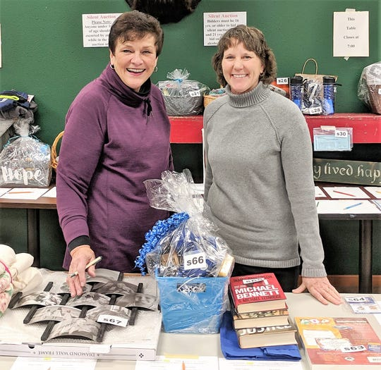 Janine Hornblad and Joanne Rauscher, who coordinated the silent auction at Holy Trinity Parish's annual auction on Nov. 10.