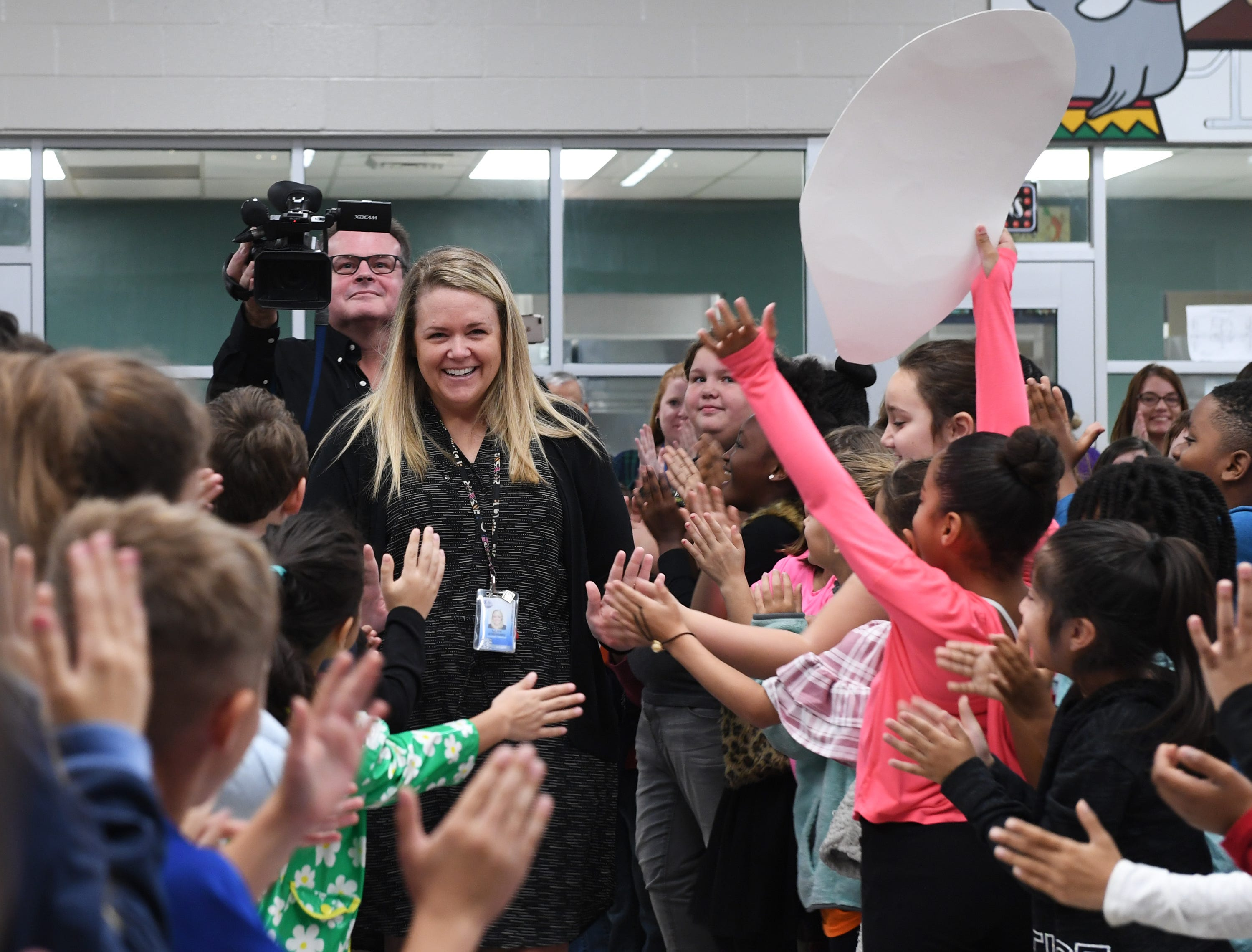 Assistant Principal Leah Stafford enters the cafeteria at Simpsonville Elementary to a crowd of students and faculty Friday Nov, 30, 2018. The crowd was gathered for the surprise announcement that Stafford is the 2019 SC Elementary Assistant Principal of the Year.