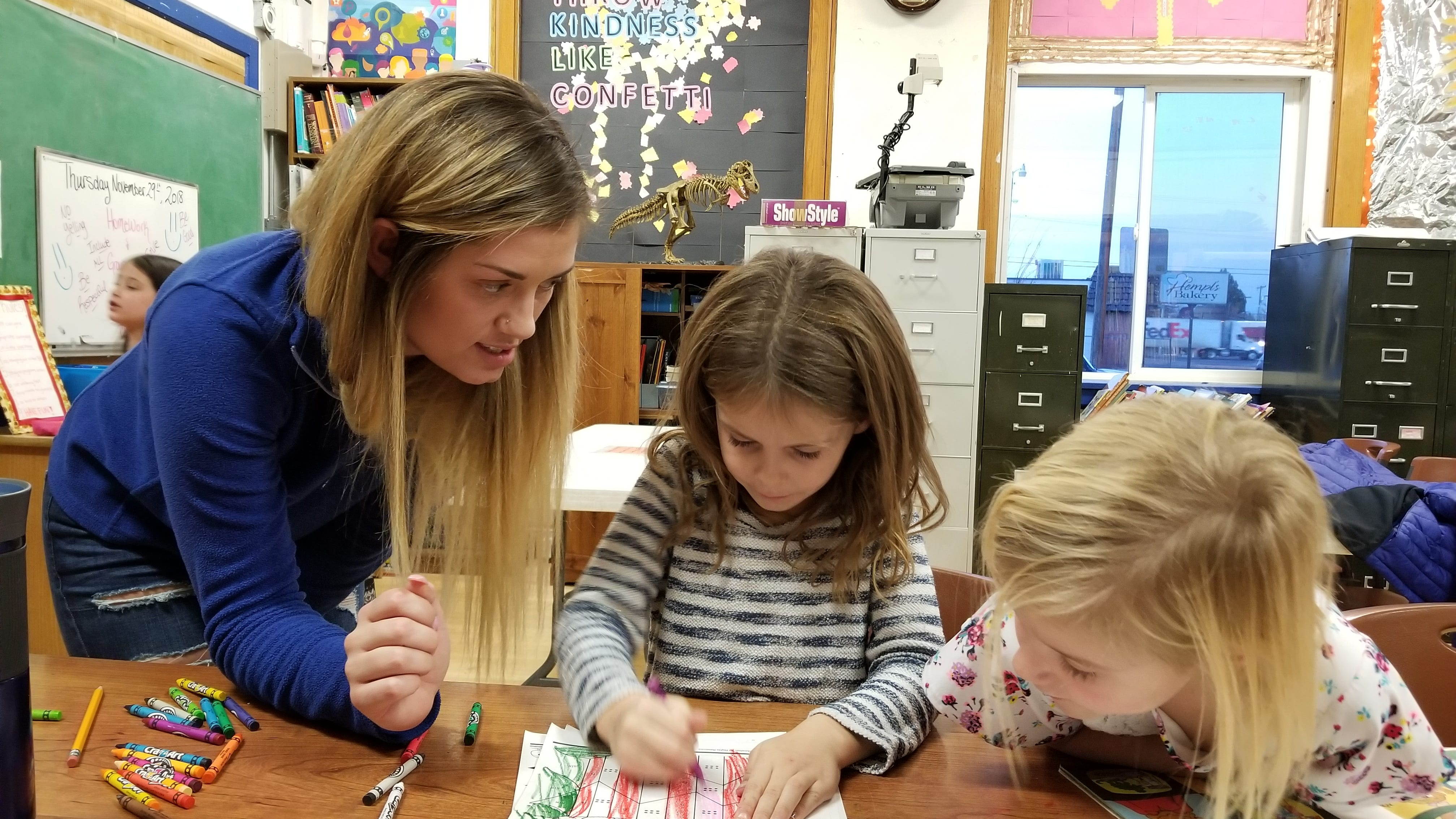 Boys and Girls Club staff member Trinity Brown helps Arizona Cave, 5, and Kinly Lawrence learn addition and counting.