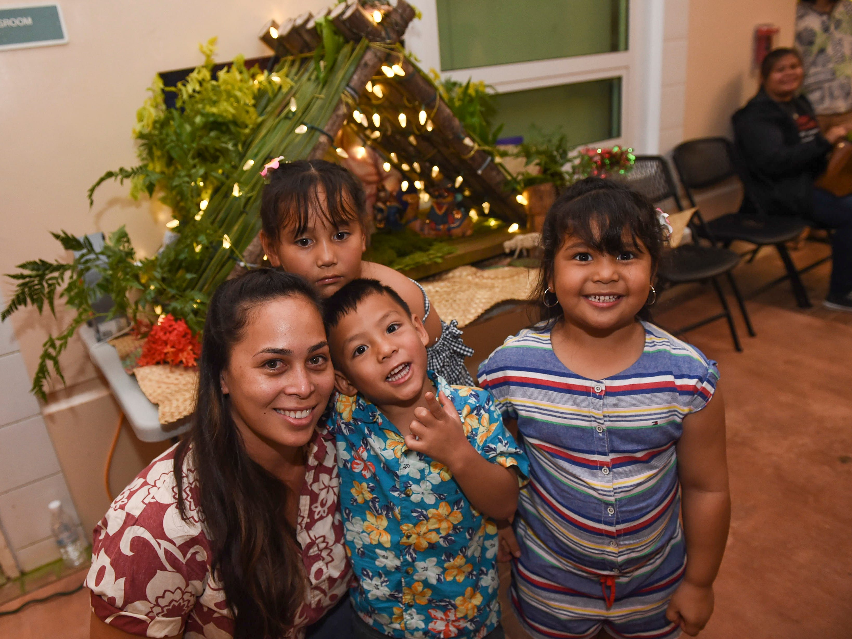 Airian Diaz, left, with her kids Aleeah, 7, top, Aycen, 4, center, and Araiah, 5, during the University of Guam Chamorro Studies Program's 2018 Christmas Celebration, Puengen Minagof Noche Buena! at the UOG Humanities and Social Sciences Building on Nov. 30, 2018.