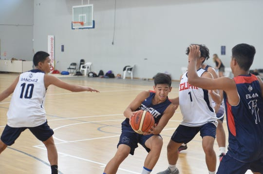 Team Guam co-captain No. 25 Matthew Santos, with ball, looks for an opening driving to the basket during team practice Nov. 28 at the GBC National Training Center in TIyan.