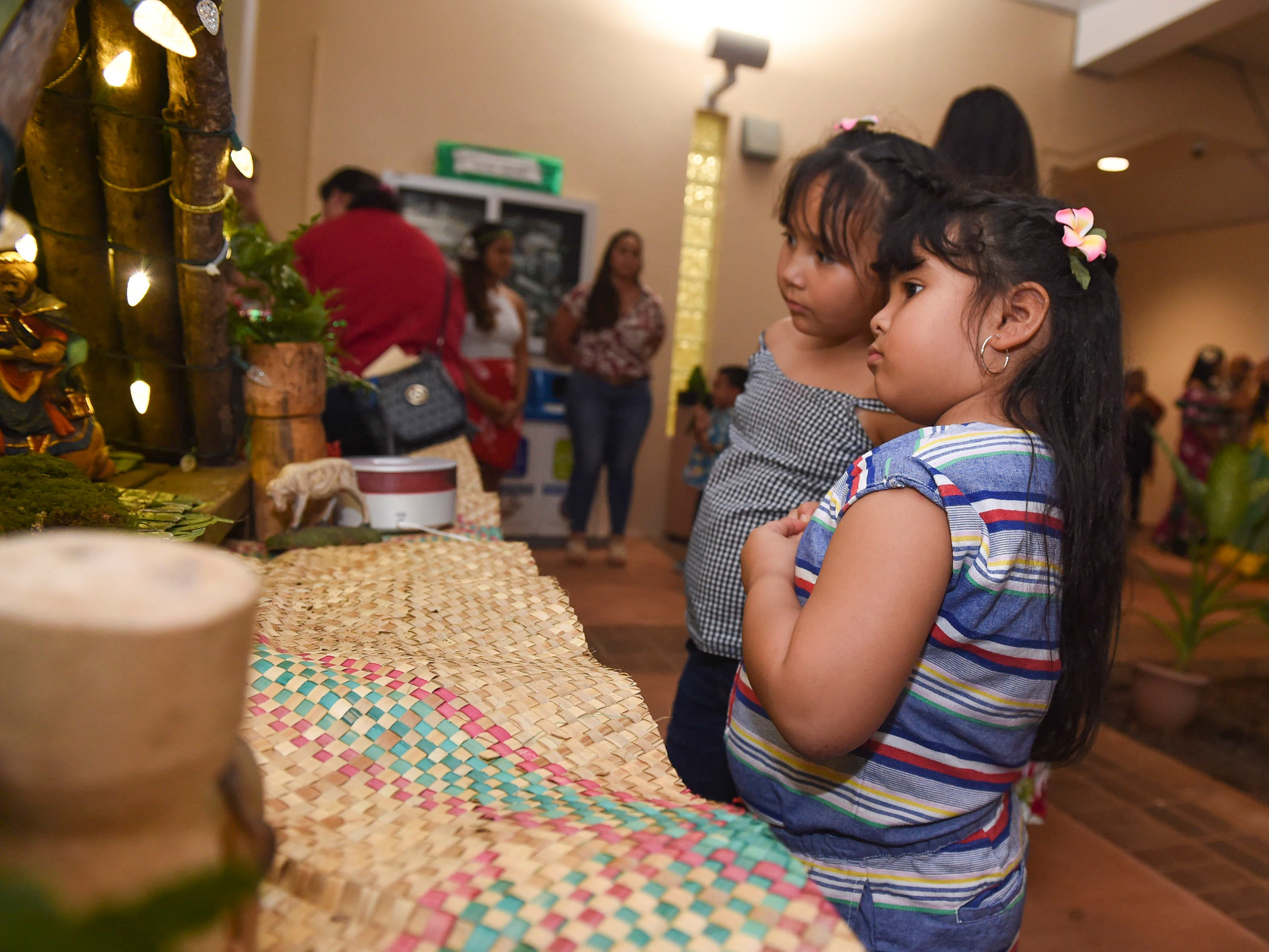 Araiah Diaz, 5, and Aleeah Diaz, 7, admire a bilen during the University of Guam Chamorro Studies Program's 2018 Christmas Celebration, Puengen Minagof Noche Buena! at the UOG Humanities and Social Sciences Building on Nov. 30, 2018.