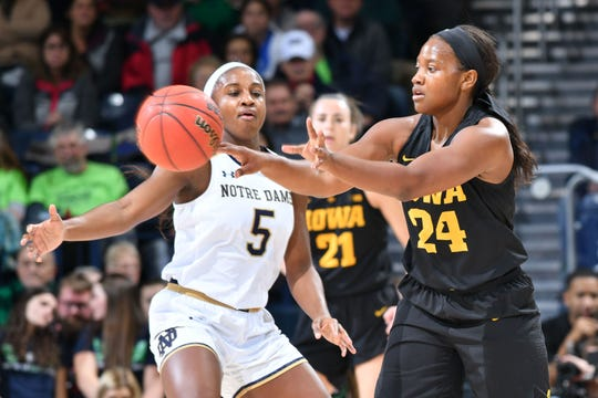 Iowa guard Zion Sanders passes as Notre Dame guard Jackie Young  defends in the first half of Thursday's game at South Bend, Ind.