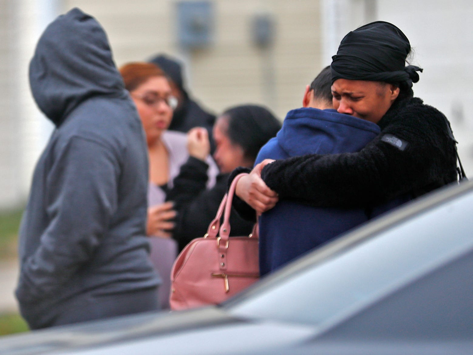 Distraught people comfort each other at the scene of a homicide in the 3800 block of Amaranth Court, Friday, Nov. 30, 2018.