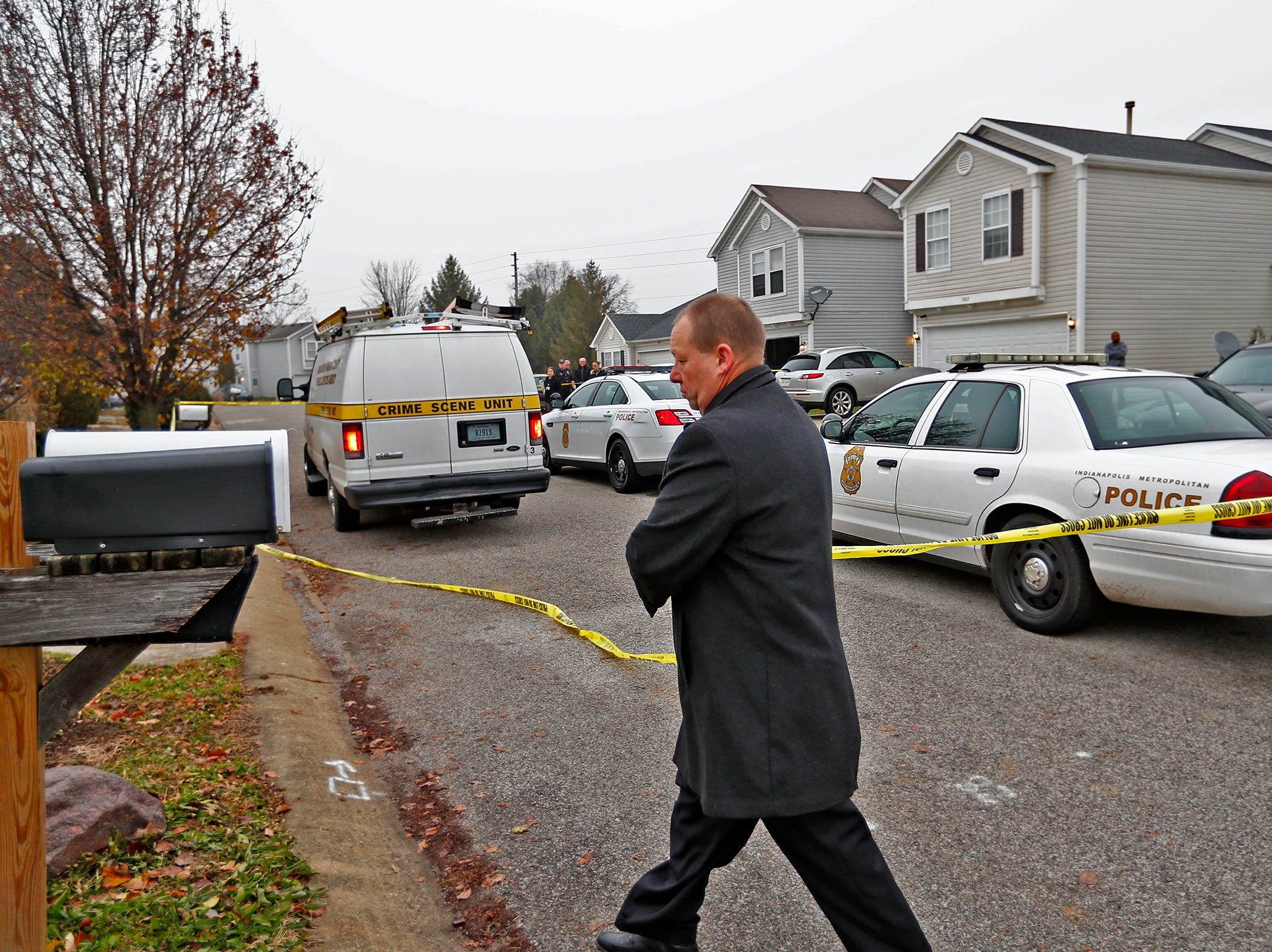 A detective replaces the police tape after letting in the Crime Scene van at the scene of a homicide in the 3800 block of Amaranth Court, Friday, Nov. 30, 2018.