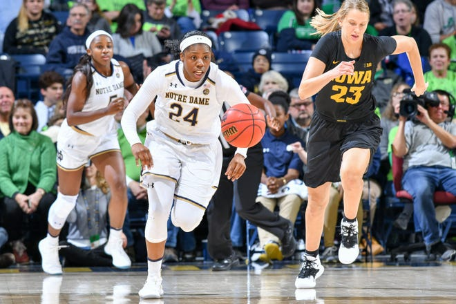 Nov 29, 2018; South Bend, IN, USA; Notre Dame Fighting Irish guard Arike Ogunbowale (24) and Iowa Hawkeyes forward Logan Cook (23) chase after a loose ball in the first half at the Purcell Pavilion.
