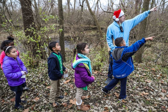 Second graders from Global Preparatory Academy point out sycamore trees during a hike led by counselor Ethan Moore at Jameson Camp in Indianapolis, Friday, Nov. 30, 2018.