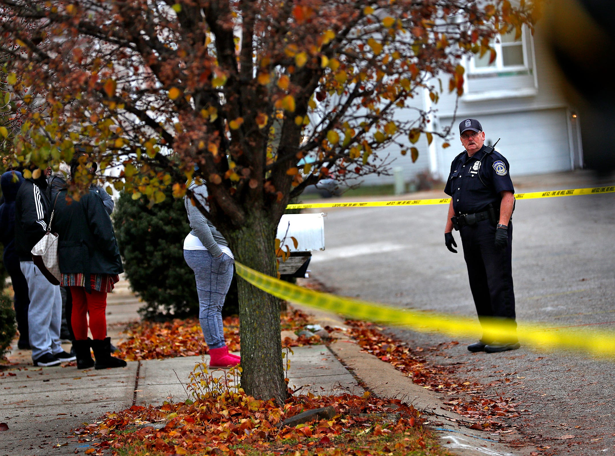 An IMPD officer talks to people watching as the investigation continues at the scene of a homicide in the 3800 block of Amaranth Court, Friday, Nov. 30, 2018.