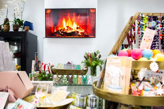 Merchandise is seen as a fireplace is played on a TV on Friday, Nov. 30, 2018, at Beno's Flowers on Iowa Avenue in Iowa City.