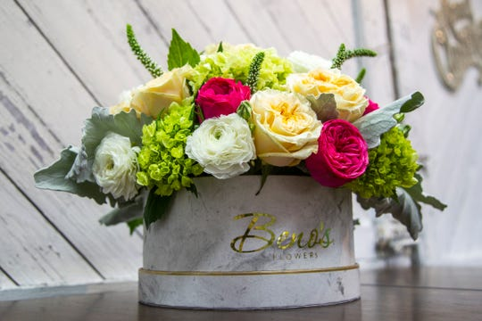 A basket of garden roses, ranunculus, mini hydrangeas, veronica and dusty miller flowers are seen on Friday, Nov. 30, 2018, at Beno's Flowers on Iowa Avenue in Iowa City.