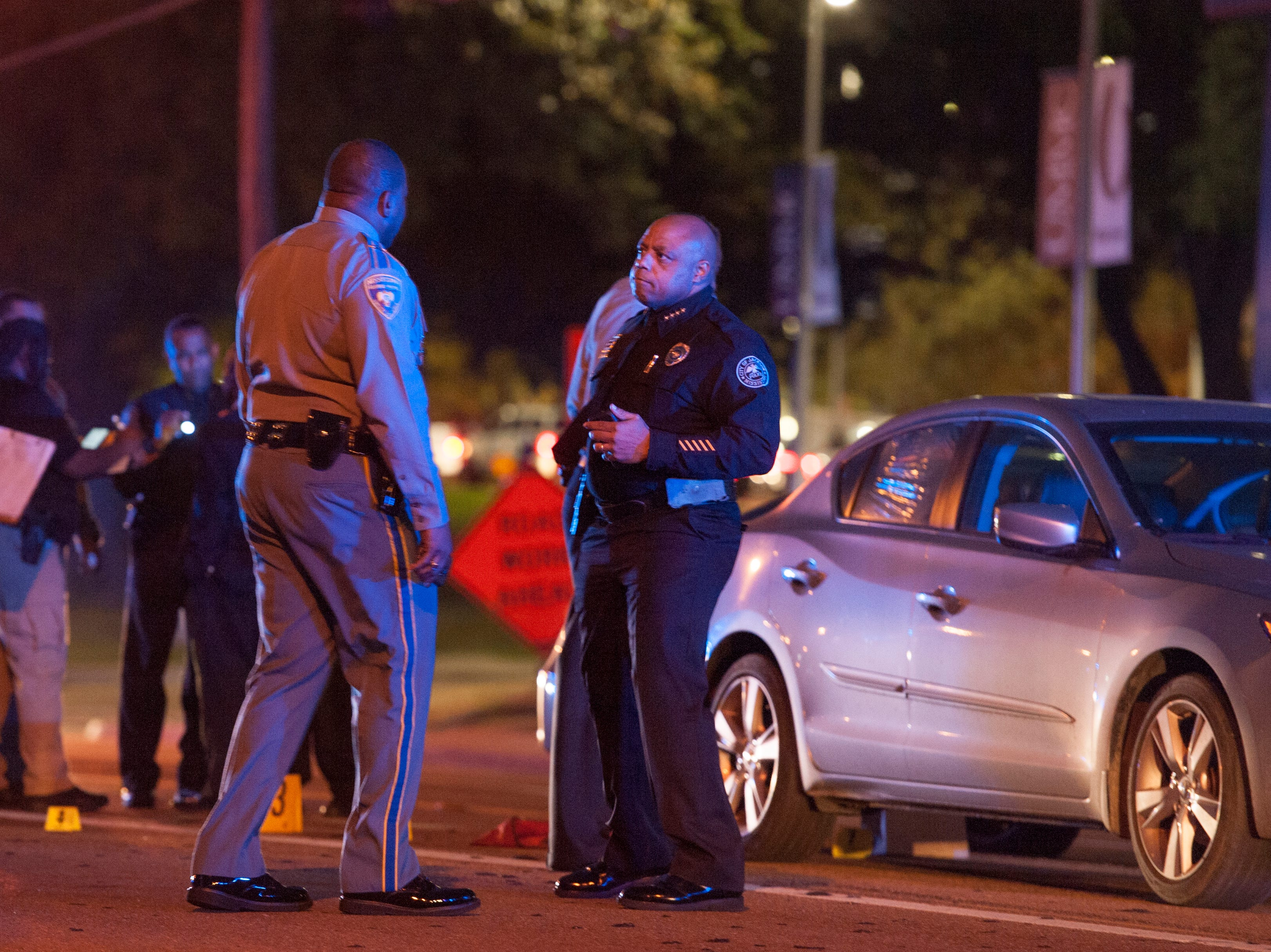 Jackson Police Chief James Davis, right of center, talks with a member of the Mississippi Highway Safety Patrol assisting in the investigation of a shooting on North State Street in front of  UMMC.