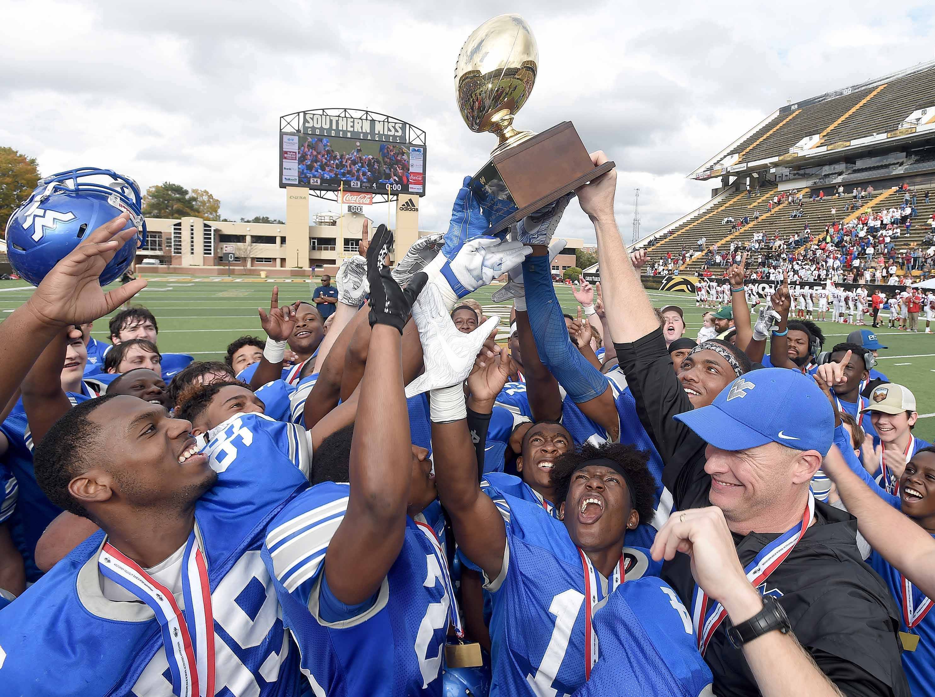 Water Valley head coach Brad Embry and the Blue Devils celebrate with the trophy on Friday, November 20, 2018, in the MHSAA BlueCross BlueShield Gridiron Classic High School Football Championships in M.M. Roberts Stadium on the University of Southern Mississippi campus in Hattiesburg, Miss.